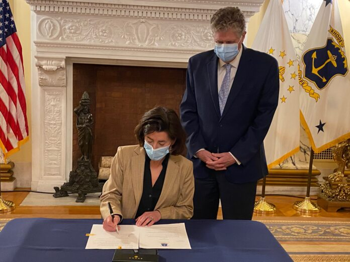GOV. GINA M. RAIMONDO signs an executive order on Monday authorizing Lt. Gov. Daniel J. McKee to oversee and manage the fiscal year 2022 state budget. / COURTESY R.I. OFFICE OF THE GOVERNOR