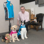 LAB MODEL: Steven Triedman, co-owner of Corky's Reflective Wear LLC, which makes highly visible and water-repellent collars and jackets for dogs, with Georgie, a yellow Lab puppy modeling the K-9 reflective wear, flanked by two stuffed models. / PBN PHOTO/MICHAEL SALERNO