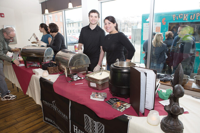 DISHING IT OUT: Ciro's Tavern in Woonsocket has participated in The Poutine Indulgence tasting competition in the past. Noah Peloquin, left, and Gina Savini, Ciro Tavern owner, work at the serving station during the 2018 competition at the Museum of Work and Culture in Woonsocket. / COURTESY JUDITH POTTER