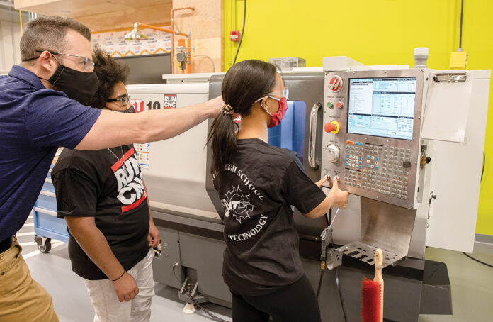 IN-CLASS INSTRUCTION: Briar Dacier, machine technology instructor at William M. Davies Jr. Career & Technical High School in Lincoln, with students Angel DeLaCruz and Mariama Barry in the machine lab. / PBN PHOTO/TRACY JENKINS