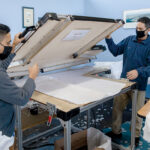 SWITCHING GEARS: Felis Franco, left, and Juan Arrojo load a sealer at Eco Global Manufacturing LLC in Providence. During the COVID-19 pandemic, the product design company switched gears to produce face shields and isolation gowns. / PBN PHOTO/TRACY JENKINS