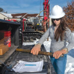 HANDS ON: Stephanie Robat, owner of FR Engineering Group Inc., prepares to examine a core sample brought up by a drill rig on a work site in Warwick. / PBN PHOTO/MICHAEL SALERNO