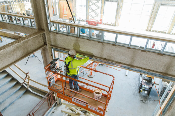 UNFINISHED: A Gilbane Inc. worker inspects a beam at the East Providence High School construction project the company has undertaken. At four stories and 300,000 square feet in size, the $190 million building is the largest K-12 project in state history. / PBN PHOTO/RUPERT WHITELEY