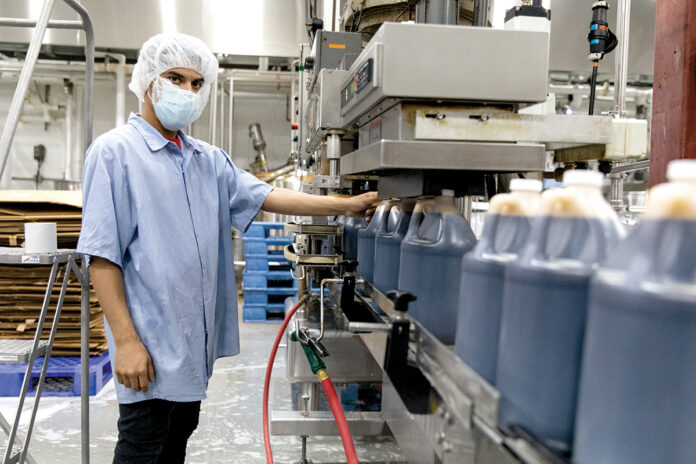 EARLY ADOPTER: Miguel Rosario on the assembly line at Finlay Extracts & Ingredients USA Inc. / PBN PHOTO/RUPERT WHITELEY