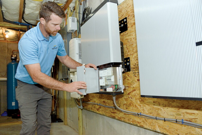 BACKUP SYSTEM: Tyler Mason, vice president and installation manager for Sol Power LLC, has installed backup batteries and a converter box in his Westerly home to provide electricity to the house during an outage. / PBN PHOTO/ELIZABETH GRAHAM