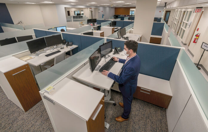 LOW HEADCOUNT: Joseph Quattrocchi, a certified public accountant at Kahn, Litwin, Renza & Co. Ltd., works in the firm's nearly empty offices in Providence. Most KLR employees continue to work from home, and the firm has struggled to determine the most optimal time to start bringing them back. / PBN PHOTO/MICHAEL SALERNO