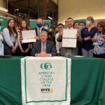 GOV. DANIEL J. MCKEE, center, on Friday signed into law legislation that eliminates the sunset provision of the Rhode Island Promise program at the Community College of Rhode Island. / COURTESY OFFICE OF GOV. DANIEL J. MCKEE