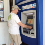 CASH FLOW: Russell Morrill of Westerly uses an ATM at The Washington Trust Co. branch in Westerly recently. Banks and credit unions are expecting to see a decline in the size of deposits as the COVID-19 crisis passes. / PBN PHOTO/ELIZABETH GRAHAM