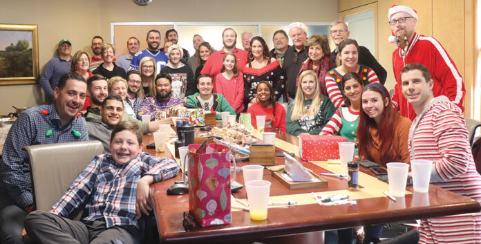 CHRISTMAS SPIRIT: New England Construction employees gather for a holiday party. / COURTESY New England Construction