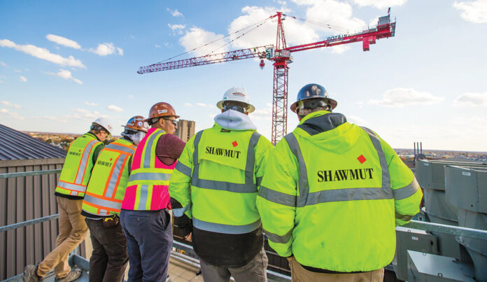 HIGH PERFORMANCE: Shawmut Design and Construction project team members overlook the construction of Brown University's performing arts center. / COURTESY SHAWMUT DESIGN AND CONSTRUCTION