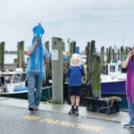 FEELING FISHY: The Town Dock employees and families celebrate with squid hats on the water. / COURTESY THE TOWN DOCK