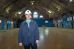 <b>Photo by Frank Mullin</b><br>Eric Greene, a project executive for The Shawmut Design and Construction Co., in the main drill hall of the Pawtucket Armory.