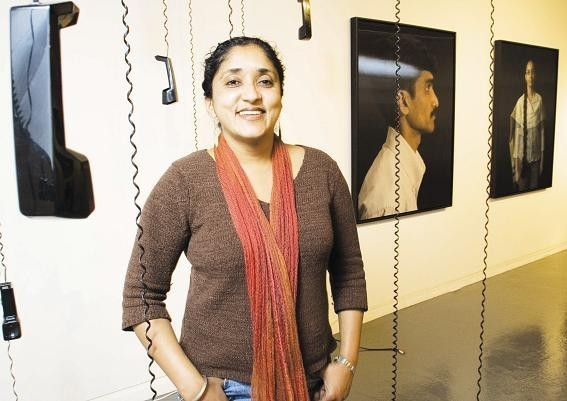 ANNU PALAKUNNATHU MATTHEW took a one-year sabbatical fromURI to document the Americanization of call-center workers in India. Her audio-visual exhibit, above, incorporating photos and recorded interviews, is on display at the URI Fine Arts Center through Dec. 10. /
