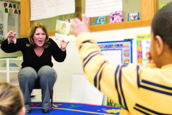 PATTY CARBONE, child care director at CFS of Newport County, reads and acts out Maurice Sendak's 'Where the Wild Things Are' for a class at the child development center. /