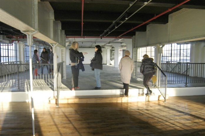 A GROUP OF prospective tenants tours the building at Conley's Wharf that the Partnership for Creative Industrial Space is leasing out. The former coal-gasification facility is being turned into offices and studios for artists and designers. /