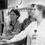 NURSES at Rhode Island Hospital monitor a patient's condition via computer, where they also can track prescription data. /