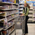A SHOPPER browses the aisles at a Wal-Mart store. The discount chain's fourth-quarter sales rose as it cut prices for the holidays. /