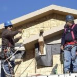 BUILDERS work on a new house in Denver. /
