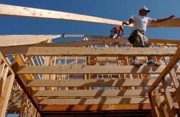 IN THE SOUTH and West, construction surged last month, boosting national figures. Above, builders frame the roof of a house in Bentonville, Ark. /