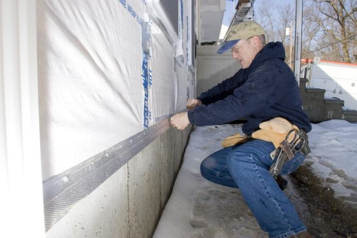 RICHARD DUMONT, owner of R.N.D. Builders in Seekonk, had to drop everything to serve a year-long tour in Iraq with the R.I. Army National Guard. Above, he works on a house his company is building in Cumberland. /