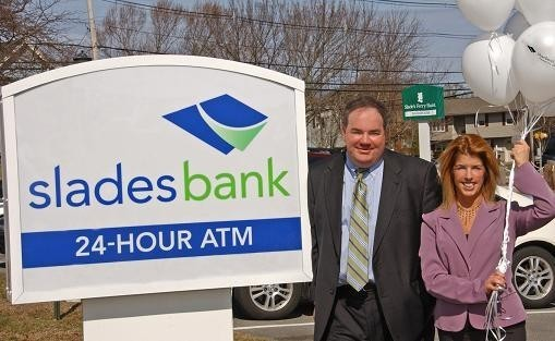 SLADES BANK's Dennis Wyatt, senior VP and director of retail banking, and Seekonk manager Lisa Russo, right, with the new sign. /