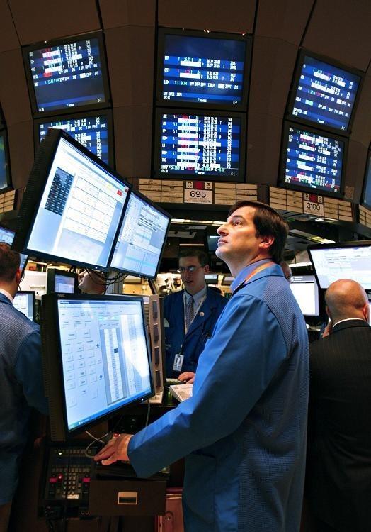 TRADERS WORK on the floor of the New York Stock Exchange last week. /