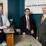 BRAVE RIVER SOLUTIONS co-founders Ernie Gaines, center, and James McAssey, right, say they have kept the firm strong by keeping its services diverse. With them is Tom Durkin, left, their senior sales representative. /
