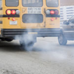 EXHAUST FUMES trail a school bus leaving a Cranston bus yard last week. Aging school buses are ranked among the worst diesel polluters. /