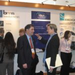 SAUL KAPLAN, executive director of the R.I. Economic Development Corporation, chats with Dr. Annie De Groot, CEO of Epivax, in front of the state's booth at BIO 2007. /