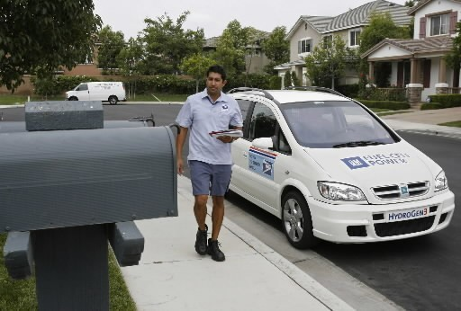 GOING UP: New postal  rates and rules take effect Monday, April 14. Above, USPS letter carrier Aldo Vasquez delivers mail in Irvine, Calif., using a fuel-cell powered minivan. /