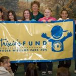 LILLIAN MCGEE, from Verizon, spends time with students from West Warwick?s Deering Middle School during their Trixie?s Fund-sponsored field trip to the Roger Williams Park Zoo. /