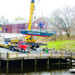A CRANE drops the Blackstone Valley Explorer in the water in Central Falls. The boat is used for tours highlighting the region?s history and natural beauty. /