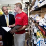 JOSEPH HINDLE, left, a senior VP at Bank Rhode Island, visits small business owner Bob Bischoff at one of his Rhode Runner running and walking accessories stores. /