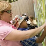 MEETING STREET student Mack, 9, is helped to attach a symbolic leaf to the CVS All Kids Can Tree House banner at Roger Williams Park Zoo during Friday's dedication at the site of the future tree house. /
