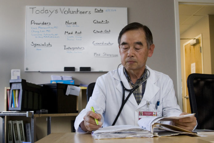 DR. CHANG LEE, a retired surgeon, volunteers at the Rhode Island Free Clinic twice a month. The clinic, which serves about 1,600 uninsured patients, has a large new facility, but not enough volunteers to meet a fast-rising demand for services. /