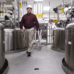 JIM RICH of Alexion Pharmaceuticals walks through an alley of buffer holding tanks at the Smithfield plant, which has been entirely renovated. /