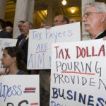 BUSINESS LEADERS protest some of legislators' budget choices at a State House rally last week. /