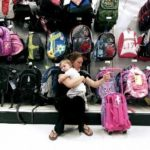 LOW TEMPERATURES and home prices continued to slow retail sales in June, the ICSC-UBS survey found. Above, Honorine Gautier holds her daughter, Bianca Gautier, 1, while shopping for a travel bag at a Target store in Miami. /