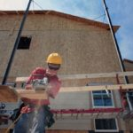 WORKERS INSTALL SIDING on a home under construction in Erie, Colo. U.S. builders started work on an unexpectedly high number of homes in June. /