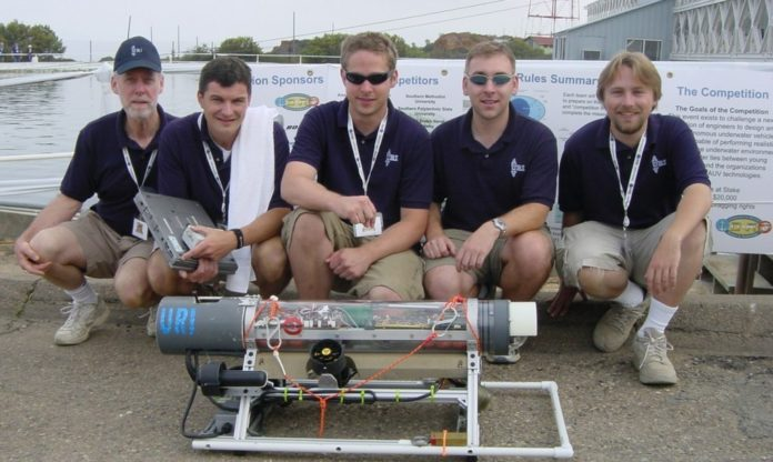 URI TEAM members pose with their second-place UAV, the RamBoat-8. From left are Coach Robert Tyce, Captain Michael Palmieri and team members Matthew Jewell, George Dossot and Jonathan Byron. /