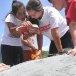 A SAVE THE BAY educator helps Bay Campers answer questions about marine life on the rocky shores of Rose Island. /