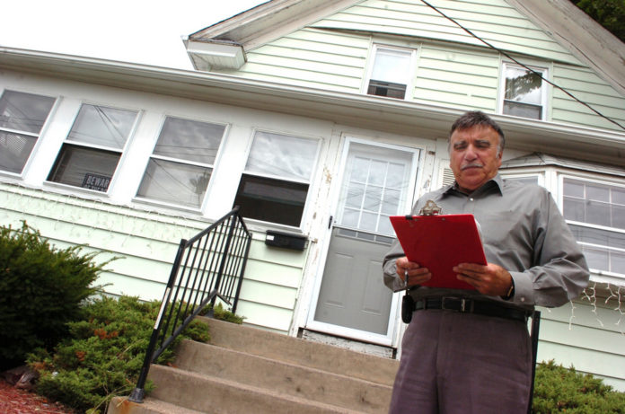 Skip Ponte reads off the legal notice announcing the auction for a property  at 440 Benefit St. in Pawtucket.  /