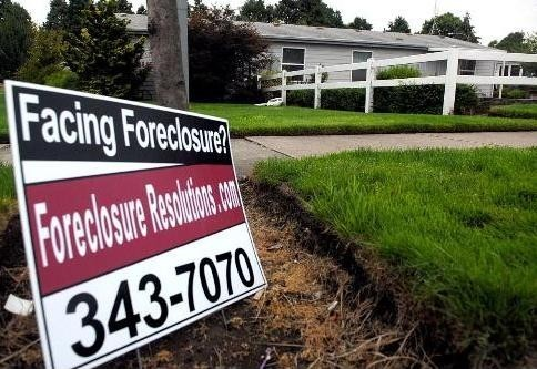 COMPARED WITH July 2006, foreclosures nationwide rose 93 percent, RealtyTrac said. Above, sign advertising foreclosure resolutions sits outside a home in Eugene, Ore., late last month.  /