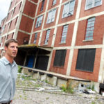 ERIC BUSCH, the American Locomotive Works site manager for Streuver Bros. Eccles & Rouse, looks over the property. The former industrial site, at the corner of Eagle and Valley streets in Providence, will be turned into shops, offices and apartments.  /