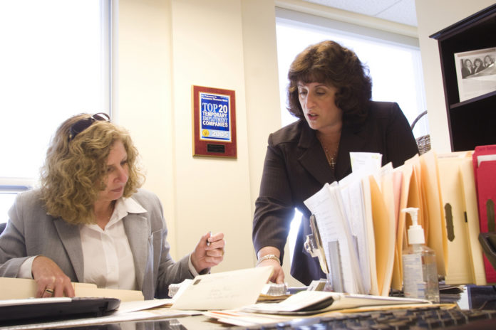 LILIANA DOLAN, right, president of Temporarily Yours Inc., goes over accounts payable with executive recruiter Lori Turchetta. /