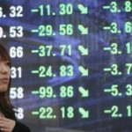 STOCK PRICES FELL around the world today. Above, a woman walks past a stock ticker board at midday in Tokyo, where the Nikkei 225 index lost 2 percent today. /