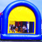 A CORPORATE GROUP takes part in a team-building exercise in an inflatable obstacle course at Fort Adams in Newport. /