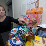 MARI-BETH BROWN chooses a snack at NetCenergy in Warwick. All snacks in the basket are low-fat, trans-fat free and were recommended by a registered nurse from the Wellness Councils of America. /