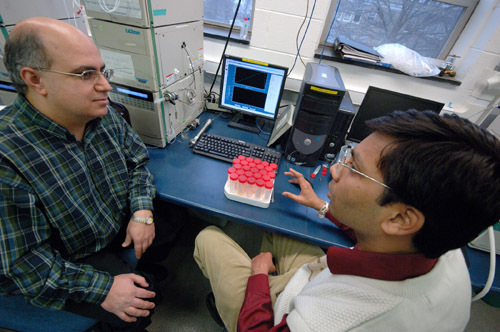 KEYKAVOUS PARANG, left, a professor at the University of Rhode Island, talks with graduate student Kitesh K. Agarwal as they test an anti-viral substance for purity. /
