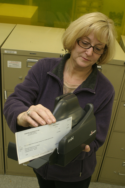 JANET CARROLL, of Fielding Manufacturing, uses a check scanner that's part of The Washington Trust Co.'s remote-deposit service. /